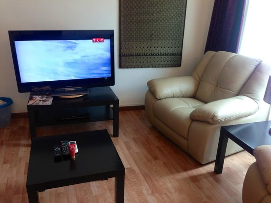 The Boutique Residence Hotel: sofa next to TV, not possible to watch TV comfortably
