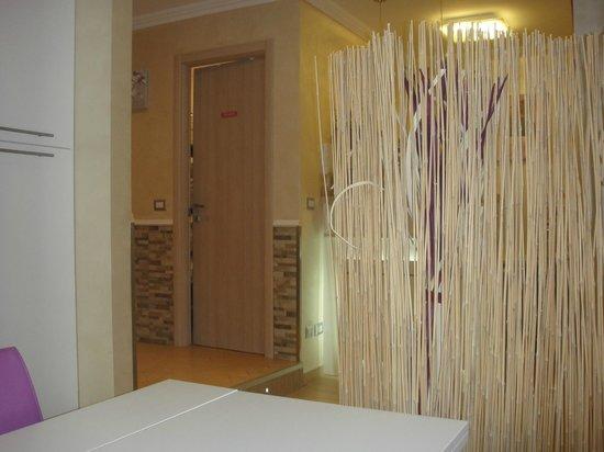Rome Kings Relais and Suite: Adelante de las 3 mesas de desayuno, unos pajas secas y el escritorio, la puerta es una hab de e