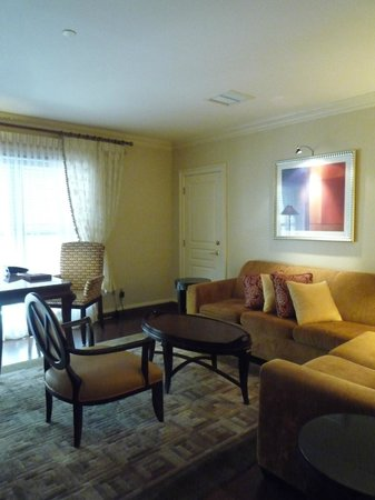 The Iroquois New York : Living room of suite with large windows, desk and comfy couches!