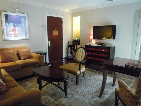 The Iroquois New York: Living room of suite with TV and bar area