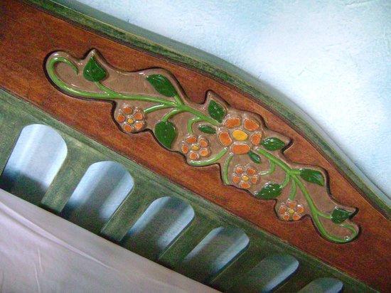 La Casa Sol Otavalo: Detalhe  da cabeceira da cama , com flores de de cerâmica.