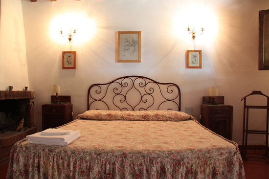 Agriturismo Il Poggio alle Ville: Canonica apartment bedroom with small fireplace