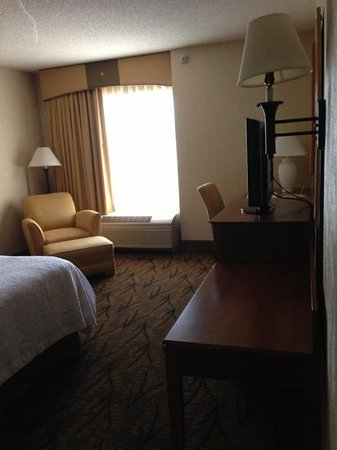 Hampton Inn Boston-Logan Airport: Bedroom with TV, desk, and seating; in addition to separate living room.