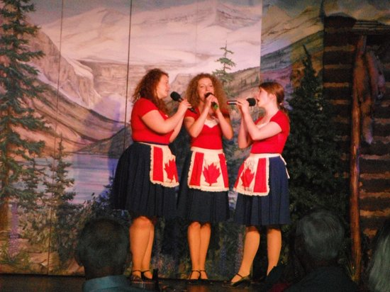 Oh Canada Eh? Dinner Show: The three female leads singing in their Canadian flag aprons.