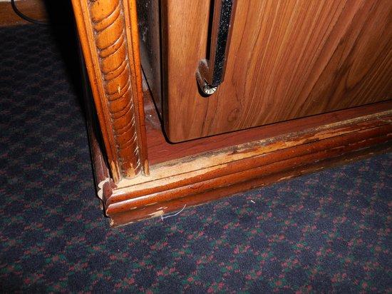 Colton Motel: broken furniture/dirt along side mini fridge