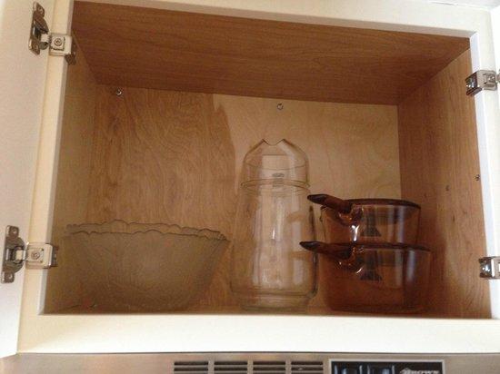 Wild Dunes Inn: Glass bowls, glass pitcher and glass pots inside cupboard.