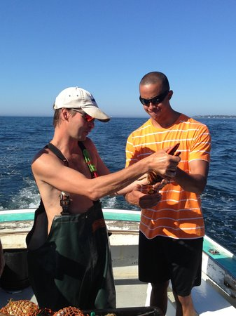 Lobster Boat Tour w/ Captain Clive Farrin : Cage showing us how to clamp on the rubber bands