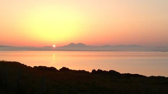 the sun rising over the Paps of Jura, port mor campsite July 2013