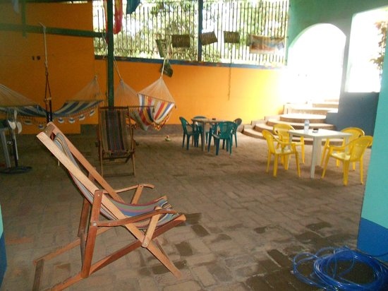 Yogi's Hostel: Middle area of the hostel with tables and hammocks