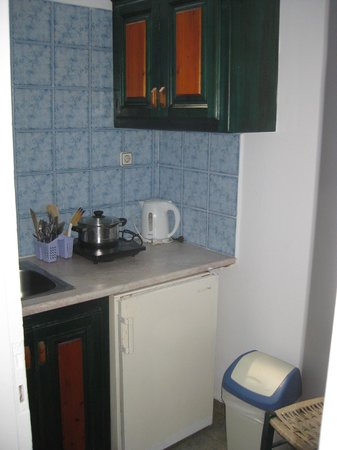 Kafieris Apartments On The Cliff : kitchen with fridge, sink, table, and one small burner to cook