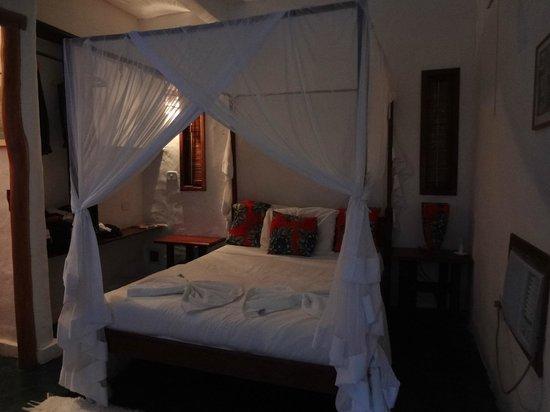 Pousada Raízes do Brasil: vista interna do quarto mostrando a cama com mosquiteiro
