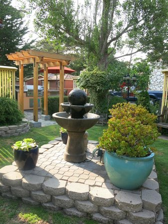 Andril Fireplace Cottages: Garden in middle of property with fountain that hummingbirds love