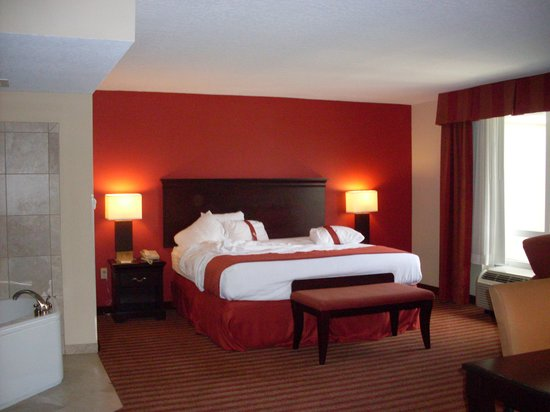 Holiday Inn Hotel & Suites Orange Park: King jacuzzi bedroom suite; living area is same size with sleeper sofa and 2nd flat screen tv