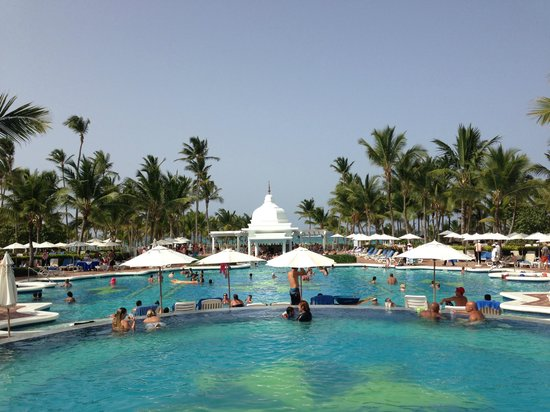Hotel Riu Palace Punta Cana: Looking from south end of pool towards beach (bar is the little building there)