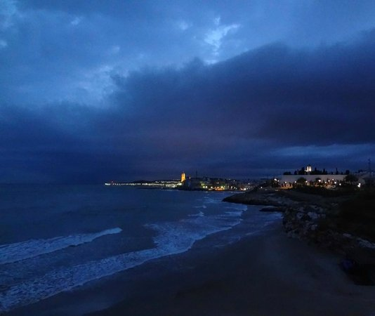 Sitges looking West just as a storm arrives and night falls.