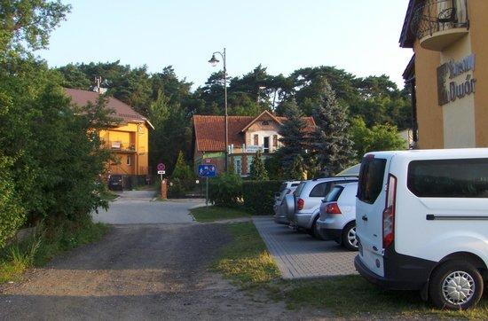 Sloneczny Dwor: jedna z części parkingu, po drugiej stronie ulicy scieżka na plażę