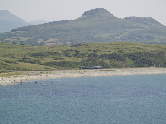 Harlech, UK: A Cambrian Coast train runs along the coast near Criccieth
