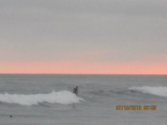 Harbor Inn & Suites Oceanside / San Diego: Surfers riding the waves under the sunset nearby the hotel