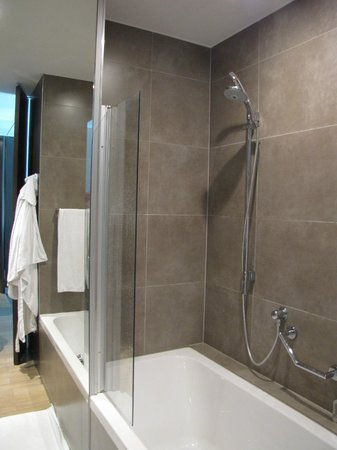 The Dominican: Modern bathroom with full size tub and rain shower