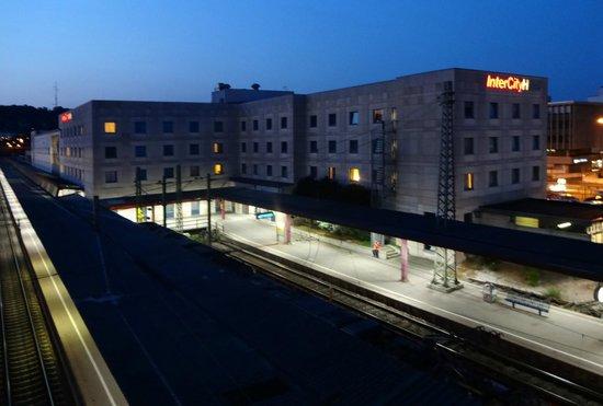 InterCityHotel Ulm: Blick von der Fußgängerüberführung auf Hotel und Bahnhof bei Nacht