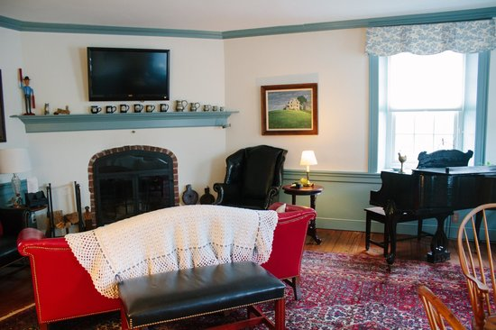Historic Smithton Inn: sitting room with TV, piano, and adjacent book and DVD library