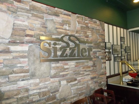 Sizzler sign across from salad bar. I liked the way it looked with the dark wood tables.