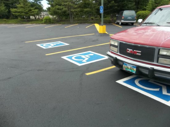 Many parking spots for disabled across from Sizzler's door and corner of building.