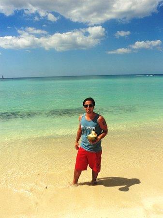 Public beach of Dominicus at Bayahibe: Dominicus - meu marido tomando agua de coco na beira mar