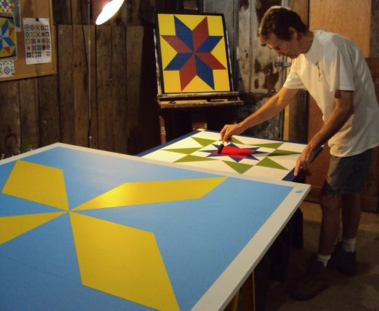 Hendersonville, Carolina del Norte: Clay at work in the studio painting a barnquilt