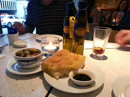 Carluccio's - Leeds: Delicious freshly made Foccacia bread with a bowl of mixed olives