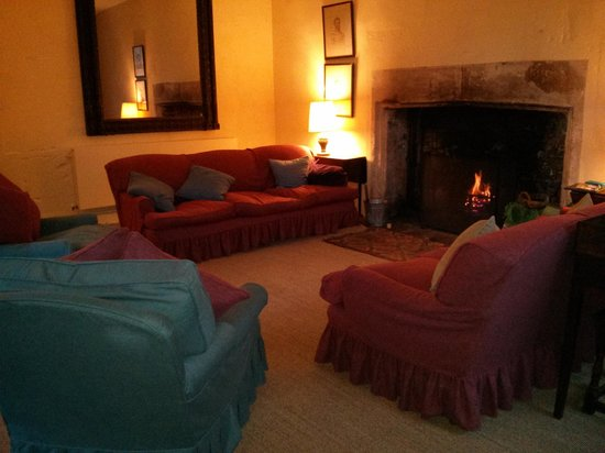 Woodspring Priory: Lounge area with lovely log fire and view over the garden