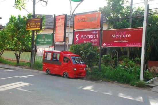 Deevana Plaza Krabi Aonang: hotel signage at ao anang road. the red vehicle is a taxi