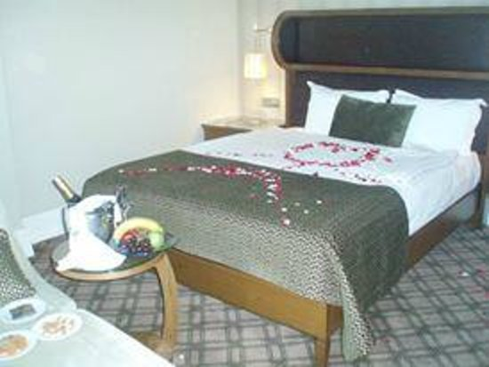 Titanic Port Hotel : view of our complimentary champagne, fruit, chocolates & nuts along w/requested rose petals on b