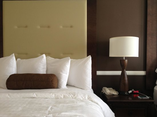 Best Western Plus San Pedro Hotel & Suites: Bedding and nightstand with alarm clock