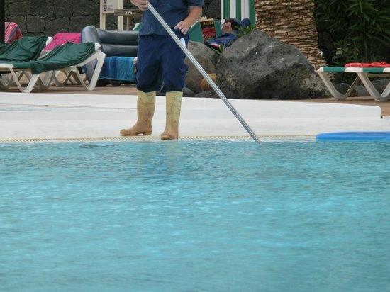 Limpiando la piscina con botas sucias fotograf a de for Que precio tiene hacer una piscina