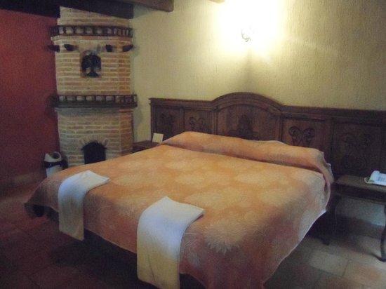 Hotel Santo Tomas: Cama y chimenea