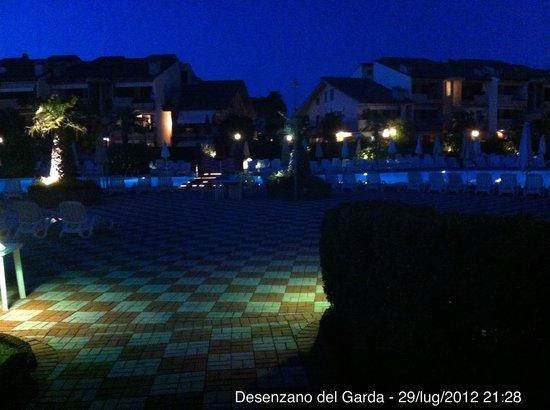 Green Residence Sirmione: Parco notturno con piscina sullo sfondo.