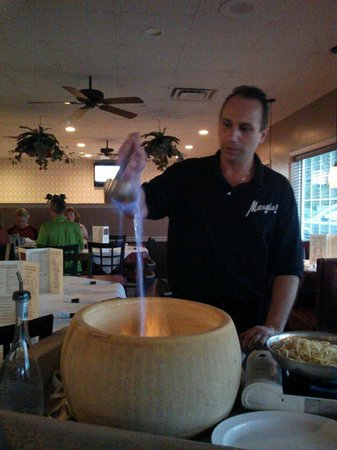 Mangia! Italian Restaurant & Pizzeria: Flambe Grappa being poured in the Parmesan