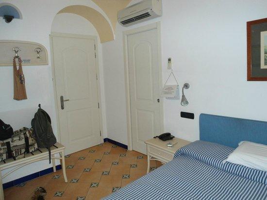 Hotel Bellevue Suites: Entrada a la habitacion y debajo del aire acondicionado puerta hacia el baño