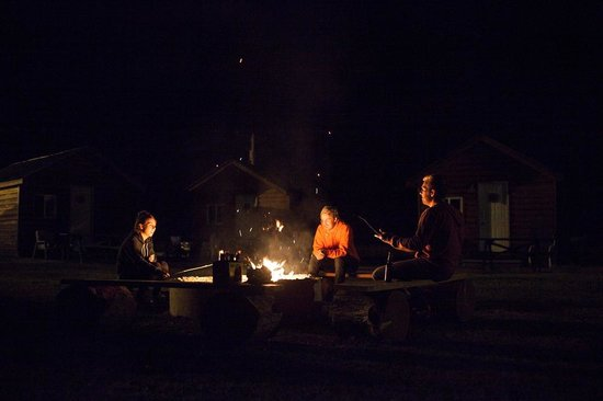 Stanton Creek Lodge: sitting around the campfire toasting marsh mellows, cabins in background