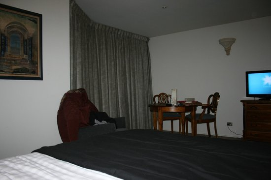 Rydges Rotorua: dining table, balcony and spa room behind the curtain