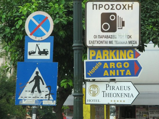 Piraeus Theoxenia Hotel: Hotel sign seen at the corner just beyond the bus stop