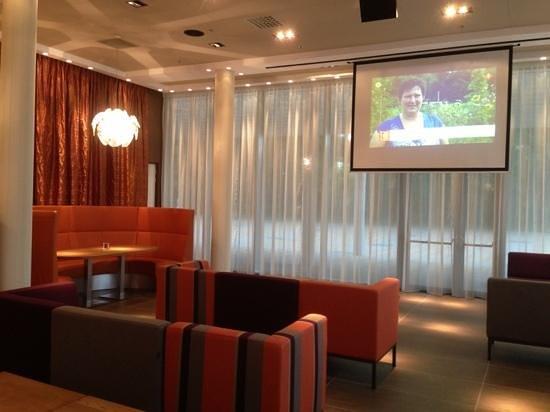 Hotel Lumen: projectiescherm in enigszins afgeschermd deel van de lobby