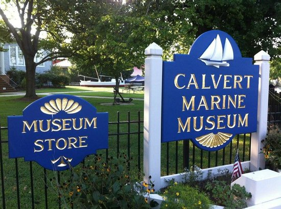 Calvert Marine Museum and Drum Point Lighthouse: Signs at entrance with Skipjack constructed by volunteers in background