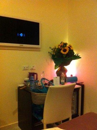 Sorrento Flats: particolare stanza con desk, tv e lampada fucsia