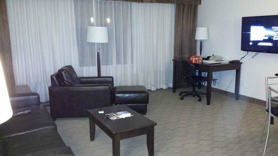 Place Louis Riel Suite Hotel: Desk, tv and living area