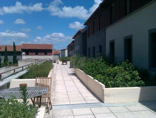 Adonis Carcassonne - Residence la Barbacane: zona común exterior de acceso a las habitaciones con mesitas