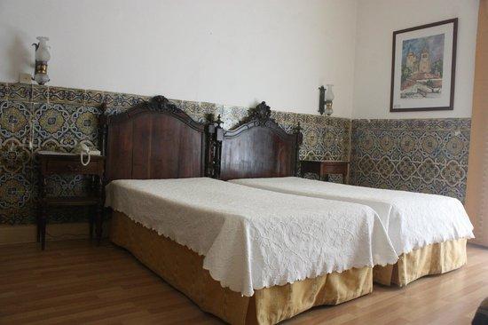 Pensao Residencial Policarpo: Habitación con muebles antiguos y paredes alicatadas