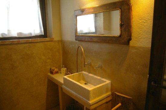 Bagno con lavello di marmo e cannella in rame foto di casale di