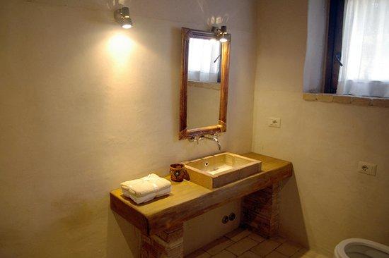 Bagno con lavabo in mattoni rossi e piano di legno foto - Piano in legno per bagno ...